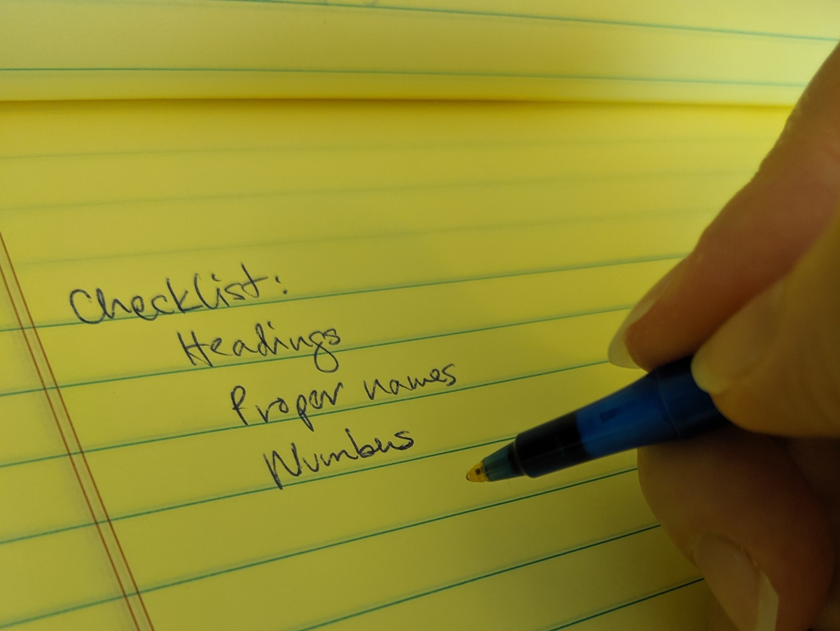 closeup of a hand holding a pen and writing a list